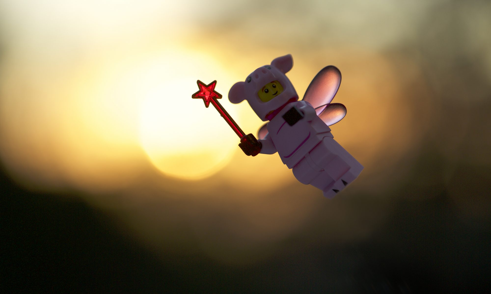 A LEGO pig mini figure with pink wings, holding a ed wand flies across the rising sun in this short depth of field outdoor toy photograph.