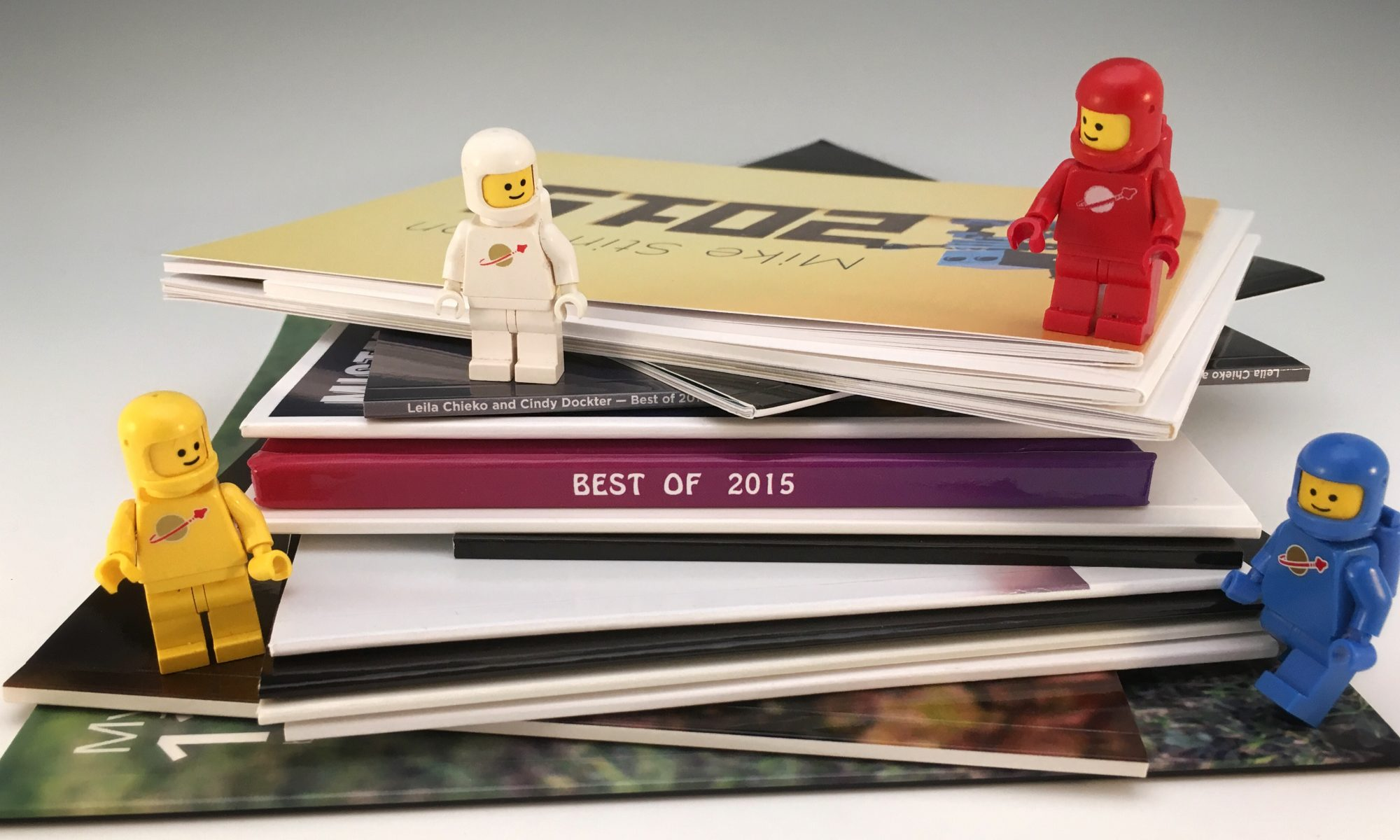 15 toy photography books in a short stack with four classic lego spacemen.